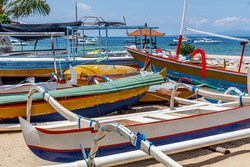 Traditional Indonesian outrigger style wooden fishing boat (jukung) on the beach at Sanur, Bali, Indonesia.