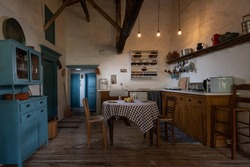 Traditional interior of old village kitchen in historic country house with stucco walls, wooden beams, oak wood furniture, vintage kitchenware