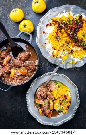 Traditional Iranian khoresh beh stew with chunks of lamb, quinces and saffron rice as top view in a cast-iron roasting dish and pewter plate  #1347346817