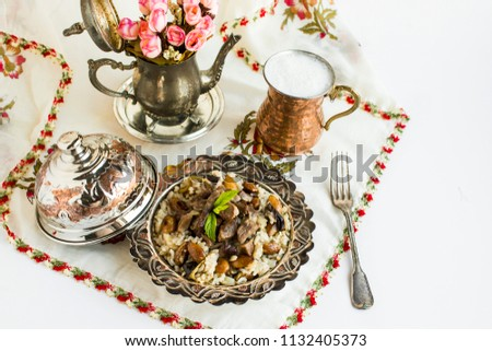 Traditional Islamic Feast,Sacrifice Festival food,cooked rice with vegetables(eggplant,onion,almond nuts) and braised meat on it.Used copper/silver set and turkish motif beaded authentic head cover. #1132405373
