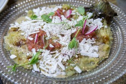 Traditional Israeli eggplant salad dish, with Feta cheese and radish, served on a glass plate