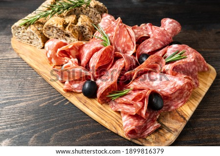 Traditional Italian antipasti salami on a wooden plate, served with olives. Food for an aperitif and dinner lunch in the restaurant.  Stock photo ©