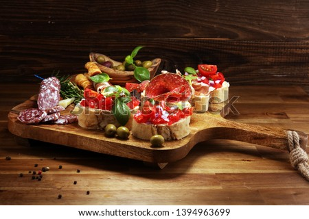 Traditional italian antipasto bruschetta appetizer with cherry tomatoes, cream cheese, basil leaves and balsamic vinegar on cutting board with prosciutto, salami, cheese,bread and olives Сток-фото ©