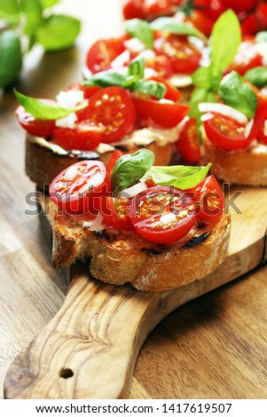 Traditional italian antipasto bruschetta appetizer with cherry tomatoes, cream cheese, basil leaves and balsamic vinegar on wooden cutting board  Сток-фото ©