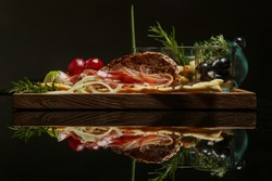 Traditional Italian appetizer board with prosciutto, bread and condiments. Exquisite dish. Creative restaurant meal concept. Haute couture food on black with reflexion. Fine dining concept.