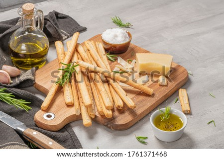 Traditional italian breadsticks grissini with rosemary, parmesan cheese, olive oil, garlic and salt on a gray background.