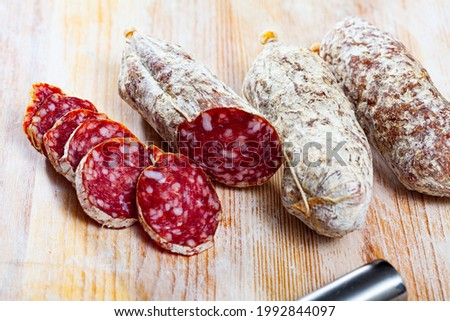 Traditional italian dry cured sausage salamini sliced on wooden surface