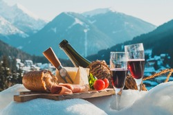 Traditional Italian food and drink outdoor in sunny winter day. Romantic alpine picnic in Dolomites with mountains background, Lambrusco cheese baguette and ham on snow.