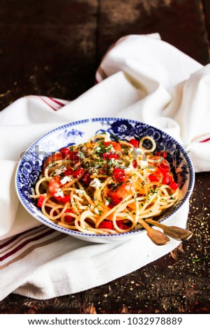 Shutterstock Traditional italian food. Bowl of homemade pasta spaghetti with fried shrimps or prawns, roasted red bell pepper, salted crumbled feta cheese, fresh dill on a wooden table, selective focus.