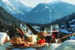Traditional Italian food outdoor in sunny winter day. Romantic alpine picnic in Madonna Di Campiglio with mountains background, North Italy.