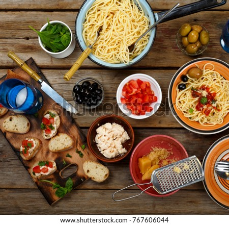 Traditional Italian food. Pasta spaghetti with tomato sauce, olives and garnish with wine on the wooden table. top veiw