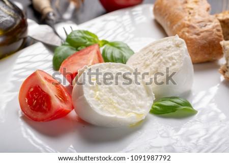 Traditional italian food - white ball mozzarella buffalo Italian soft cheese with cheese knife, tomato, basil, olive oil