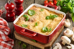 Traditional Italian lasagna with meat, mushrooms, tomatoes and cheese, decorated with basil in a red ceramic form. Old wood background. Selective focus