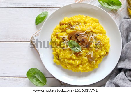 Traditional Italian risotto with mushrooms, saffron and parmesan cheese on white wooden background. Top view with copy space.