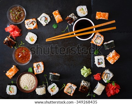 Traditional Japanese food - sushi, rolls and sauce on a dark background. Top view