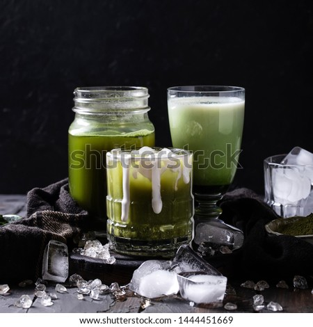 Traditional Japanese Matcha tea together with Iced Matcha Latte drink decorated with ice cubes, matcha powder, napkin and cream over rustic wooden background. Copy space. Copy space. Square image