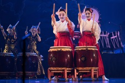 Traditional Japanese performance. Group of actresses in traditional kimono and fox masks drum taiko drums on the stage.