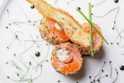 traditional japanese rolls with salmon and philadelphia cheese sesame and red caviar on a white plate with decor
