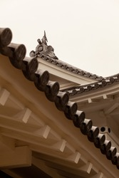 Traditional Japanese roof design known as noyane or hidden roof with multiple layers of slanted roofs formed by rugged tiles. This artistic vintage architectural style is common in temples and shrines