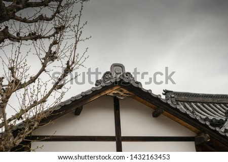 Traditional Japanese  roofline architecture with gatou style eaves against a grey overcast sky