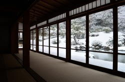 Traditional Japanese style room with view over snowy winter landscape from panorama windows