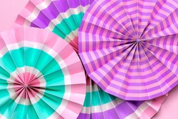 Traditional Japaneses festival paper fan with pink, turquoise, white stripes Birthday party, celebration holidays concept Abstract background Wall decor
