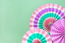 Traditional Japaneses festival paper fan with pink, turquoise, white stripes on green background Birthday party, celebration holidays concept Abstract background Wall decor