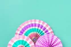 Traditional Japaneses festival paper fan with pink, turquoise, white stripes on green background