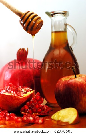 Traditional Jewish food, apple, honey and pomegranate for the holiday of Rosh Hashanah are isolated on white.