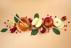 Traditional Jewish holiday New Year. Happy Rosh Hashanah. Apples, pomegranates and honey on a yellow background. Place for your text.