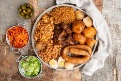 Traditional Jewish Shabbat  Meal (Cholent Hamin) slow cooked beef, potato, beans, brown eggs, wheat, chick pea and onion, served with salads and pickles