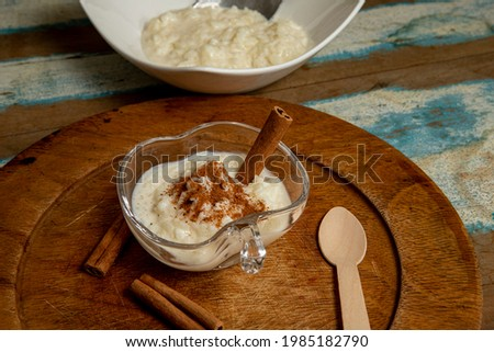 Traditional June party brazilian dessert made of rice and condensed milk called arroz doce decorated with cinnamon on colorful wooden table Foto stock ©