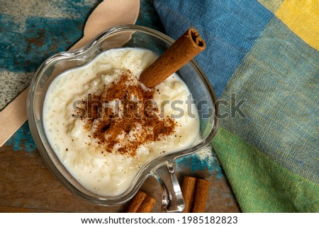 Traditional June party brazilian dessert made of rice and condensed milk called arroz doce decorated with cinnamon on colorful background Foto stock ©