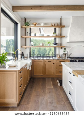 Traditional kitchen detail in new luxury home with farmhouse sink, hardwood floors, wood beams, large island and quartz counters
