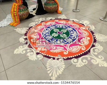 Traditional Kolam. Kolam is a form of drawing that is drawn by using rice flour, chalk, chalk powder or rock powder, often using naturally or synthetically colored powders.