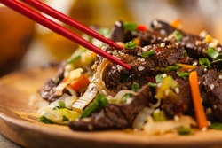 Traditional Korean Bulgogi dish.  Thinly cut, grilled beef, served with rice and vegetables. Front view. Natural wooden background. Close up.