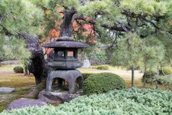 Traditional lantern made of stone in Japanese garden of Nijo Castle in Kyoto which when lit, it is considered as an offering to Buddha.