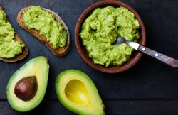 Traditional latinamerican mexican sauce guacamole in clay bowl, cut half avocado and avocado sandwiches on dark background. Top view