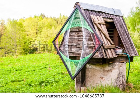 Traditional Lithuanian village with a bit of new waves and style. Old concrete well with wooden roof, metal kettle and psychedelic rhombus decoration on it. #1048665737