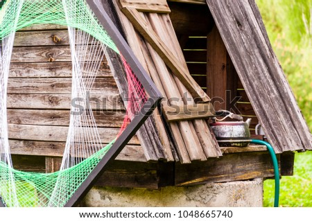 Traditional Lithuanian village with a bit of new waves and style. Old concrete well with wooden roof, metal kettle and psychedelic rhombus decoration on it. #1048665740