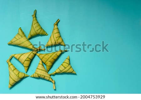 Traditional Malay rice cakes, known as 'Ketupat Palas'; lying on turquoise background. Copy space for text or words. A selective focus photo of 'Ketupat Palas'. Foto stock ©