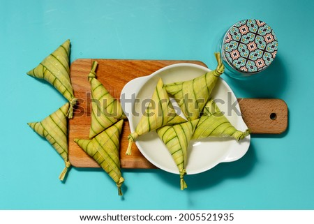 Traditional Malay rice cakes, known as 'KETUPAT PALAS', with decorations (wooden cutting board, white bowl and cookies jar); on turquoise background. A selective focus photo of 'KETUPAT PALAS'. Foto stock ©