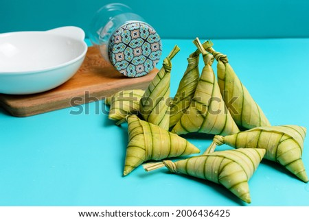Traditional Malay rice cakes, locally known as 'KETUPAT PALAS', with cutting board, cookies jar and white bowl; on turquoise background. A selective focus photo of 'KETUPAT PALAS'. Foto stock ©