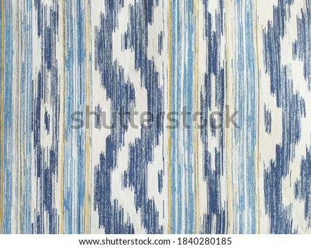 """Traditional Mallorcan fabric texture with a pattern in the shape of blue and white tongues. Cushion fabric background made with natural fiber and bluish tint. """"IKAT"""", typical majorcan fabric pattern."""