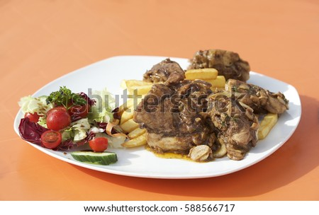 Traditional maltese food - rabbit with fresh vegetables and chips isolated on orange background. Malta. Fenek. Stock fotó ©