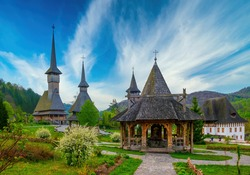 Traditional Maramures wooden architecture of Barsana monastery, Romania. Picturesque sky