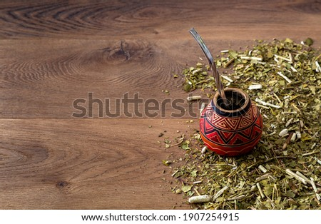 Traditional mate made of calabash over a wooden table with yerba mate scattered over it. Stockfoto ©