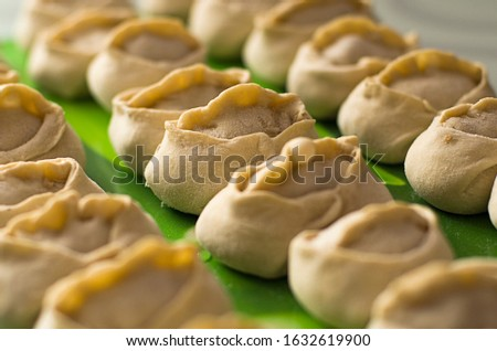 Traditional meat dish of the peoples of Central Asia. National cuisine. Russian cuisine. Minced meat wrapped in a thin dough. Handmade. Traditional Turkish Manti with yoghurt and Vinegar.