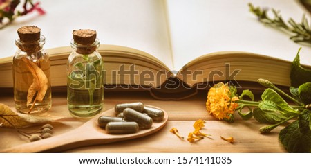 Traditional medicine for the preparation of medicines with capsules and healing essences and recipe book on wooden table. Front view. Panoramic composition. Vintage style