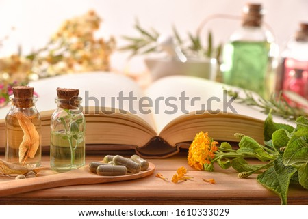 Traditional medicine for the preparation of medicines with capsules and healing essences and recipe book on wooden table. Front view. Panoramic composition.